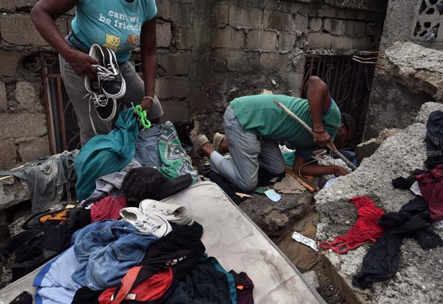 17 August 2021, Haiti, Les Cayes: People search for belongings in a damaged house's rubble after a massive earthquake in Les Cayes, Haiti. The death toll from the earthquake that hit Haiti at the weekend has risen by more than 500 to 1,941. Photo: Carol G