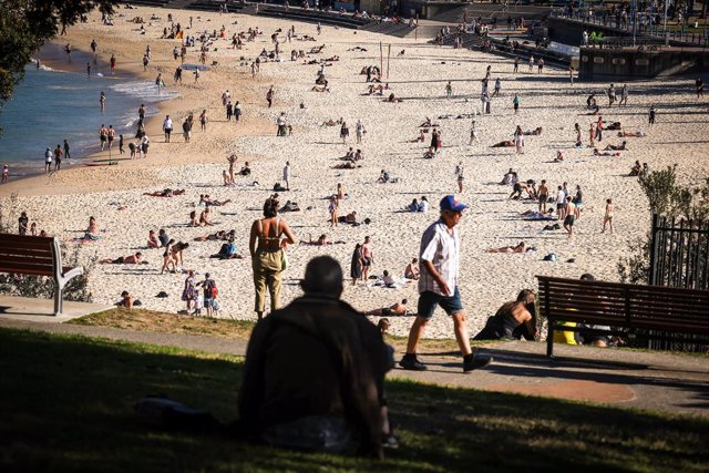 Beachgoers sit and walk at Coogee Beach in Sydney, Sunday, August 15, 2021. NSW reported 415 new locally acquired cases of COVID-19 and four more people have died as the entire state continues in lockdown. (AAP Image/David Gray) NO ARCHIVING