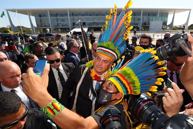 HANDOUT - 12 August 2021, Brazil, Brasilia: Brazilian President Jair Bolsonaro (C) poses for a selfie with indigenous accessories as he arrives for a meeting with indigenous representatives. Photo: Isac Nobrega/Palacio Planalto/dpa - ATENCIÓN: Sólo para u