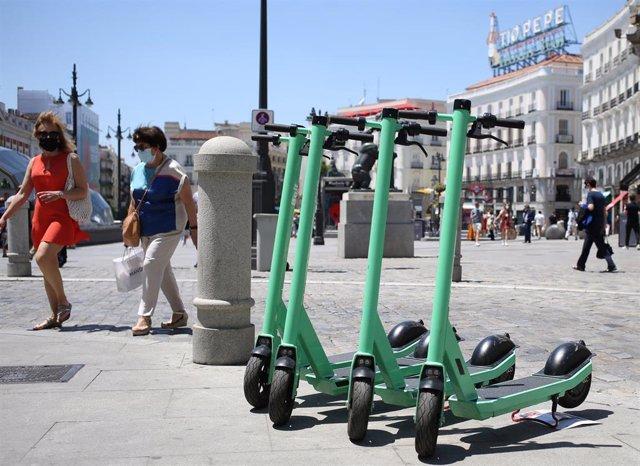 Archivo - Varios patinetes estacionados en una calle céntrica de Madrid