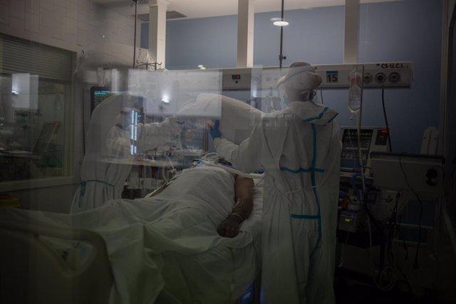 Archivo - Arxiu - Treballadors sanitaris protegits atenen a un pacient en una UCI (Arxiu)