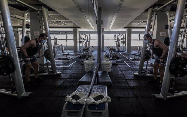 Archivo - Un hombre hace deporte en las instalaciones de un gimnasio.