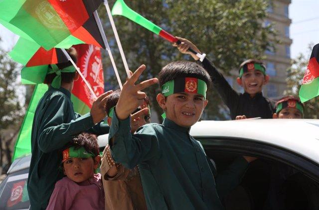 Archivo - Niños con banderas celebrando la independencia de Afganistán