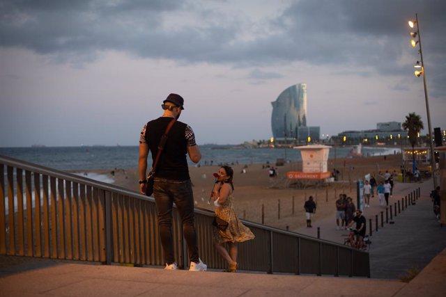 Un home fa fotos a una dona enfront de la platja de la Barceloneta, a 4 d'agost de 2021, a Barcelona, Catalunya (Espanya). Barcelona afronta aquest estiu una temporada turística marcada per la cinquena ona de la pandèmia per Covid-19 a Espanya, que ha re
