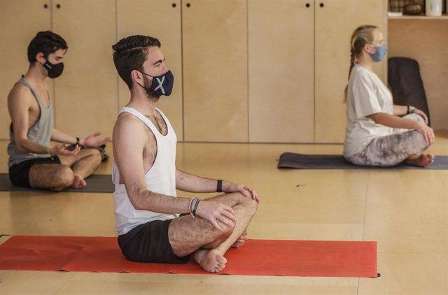 Archivo - Varios alumnos realizan yoga en las instalaciones de un gimnasio.