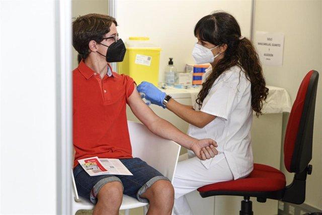Una sanitaria vacuna a un adolescente con la primera dosis de la vacuna Moderna en la Ciudad de las Artes, a 16 de agosto de 2021, en Valencia, Comunidad Valenciana, (España).