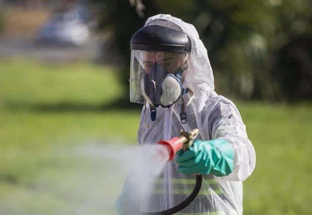 Archivo - Un trabajador durante las labores de fumigación contra los mosquitos causantes del virus del Nilo en Coria del Río