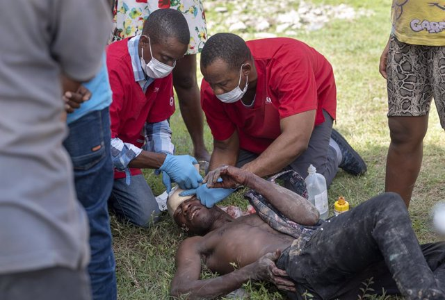 19 August 2021, Haiti, Maniche: Medical workers treat an injured man at a mobile medical clinic, set up by Kansas City-based Heart to Heart International, in a compound outside the office of the mayor of Maniche near the epicentre of the earthquake. With
