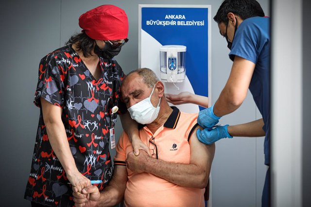 Archivo - 11 July 2021, Turkey, Ankara: A nurse holds the hands of a man being injected with a dose of Biontech's Corona vaccine at a vaccination center in Kizilay Square. Photo: Tunahan Turhan/SOPA Images via ZUMA Wire/dpa
