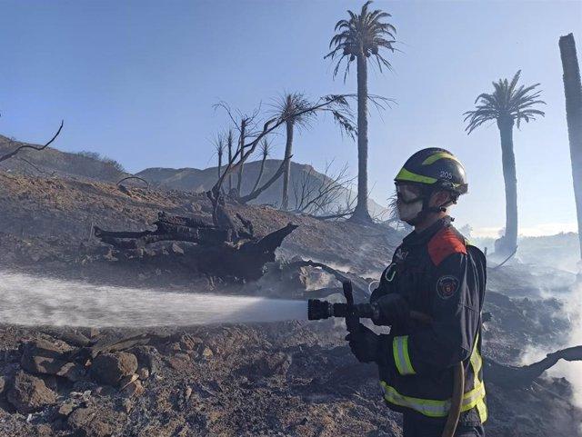 Archivo - Un bombero realiza tareas de enfriamiento en un incendio