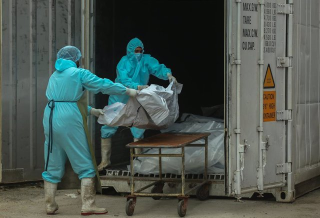 20 August 2021, Sri Lanka, Colombo: Helath workers in protective suits carry a body of a Coronavirus victim from a freezer storage to a trolley at the Institute of Forensic Medicine & Toxicology in Colombo. Photo: Pradeep Dambarage/ZUMA Press Wire/dpa