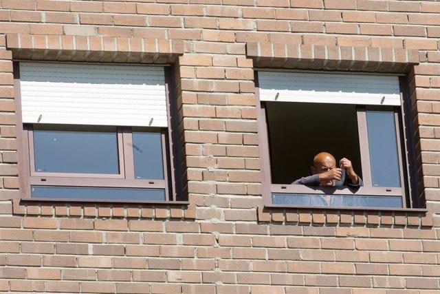 Un ancià col·loca el seu mascarilla en la finestra de la seva habitació de la residència de majors
