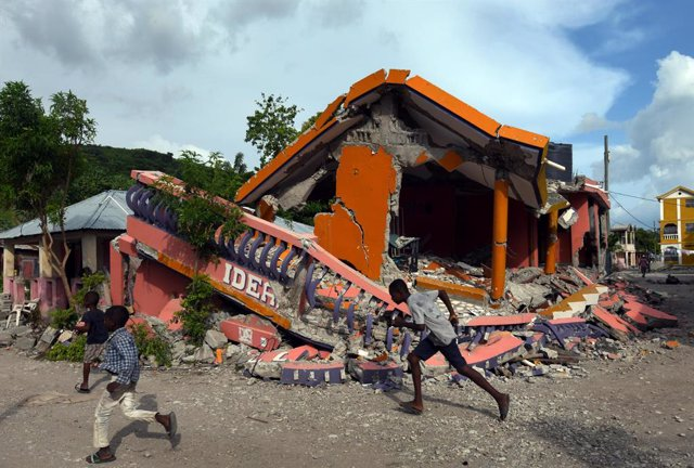 19 August 2021, Haiti, Les Cayes: Children plays in front of a damaged house after a massive earthquake in Les Cayes. Photo: Carol Guzy/ZUMA Press Wire/dpa