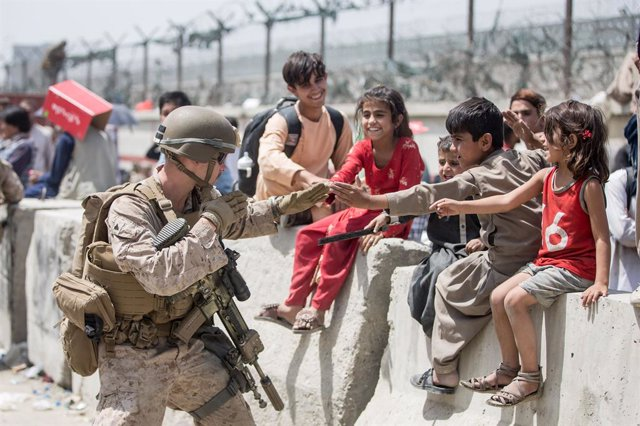 20 August 2021, Afghanistan, Kabul: A US Marine soldier plays with children as Afghan civilians wait to board an aircraft during the evacuation process at Hamid Karzai International Airport. Photo: Samuel Ruiz/U.S. Marine Corps via ZUMA Wire/dpa