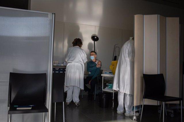 Archivo - Arxivo - Una infermera bovina a un professional sanitari amb la vacuna de Pfizer-BioNtech contra el COVID-19 a l'Hospital de la Santa Creu i Sant Pau de Barcelona.