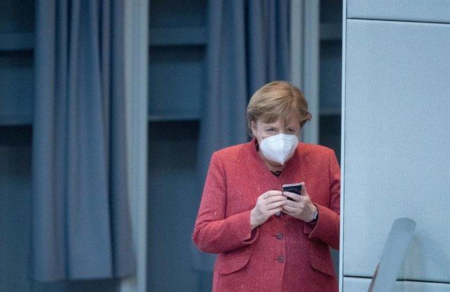 Archivo - Angela Merkel revisa su teléfono móvil en el Bundestag