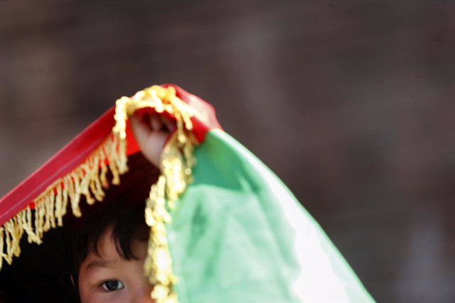 21 August 2021, Italy, Rome: A child stand under a flag oif Afghanistan during a demonstration in Rome's Piazza della Repubblic, in solidarity with Afghanistan after the Taliban takeover. Photo: Cecilia Fabiano/LaPresse via ZUMA Press/dpa