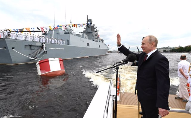 HANDOUT - 25 July 2021, Russia, St. Petersburg: Russian President Vladimir Putin waves to soldiers sailing past during a naval parade at the Neva River to mark the Russian Navy Day. Photo: -/Kremlin/dpa - ATTENTION: editorial use only and only if the cred