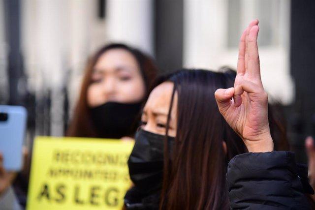 Archivo - Una mujer hace el gesto de los tres dedos levantados que se ha convertido en el símbolo de las protestas contra la dictadura en Birmania