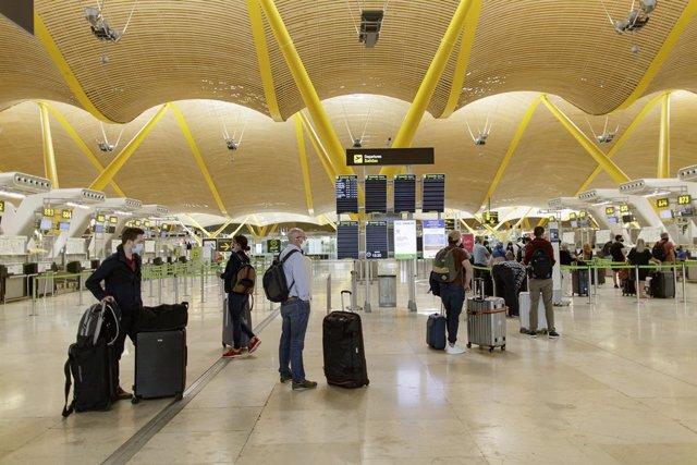 Archivo - Pasajeros con sus maletas en las instalaciones de la Terminal T4 del Aeropuerto Adolfo Suárez Madrid-Barajas,