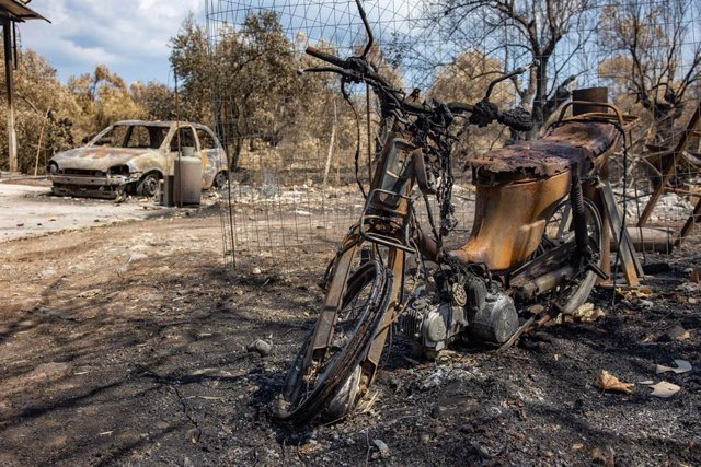 19 August 2021, Greece, Evia Island: A burnt motorcycle and car are pictured near Agia Anna, after wildfires kept burning almost for 10 days. Photo: Nik Oiko/SOPA Images via ZUMA Press Wire/dpa