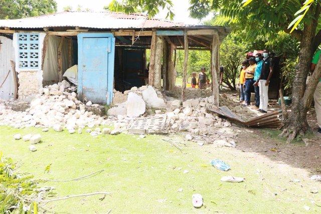 Varias personas observan los daños causados en un edificio tras el terremoto en Haití.