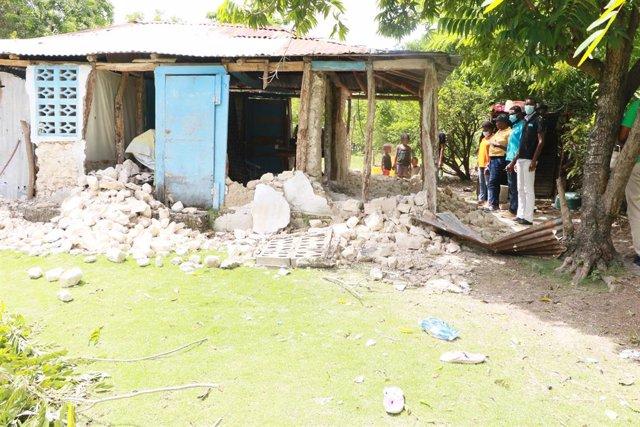Varias personas observan los daños causados en un edificio tras el terremoto en Haití