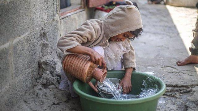 Una niña de 14 años lava los platos en un campo de desplazados en Yemen.