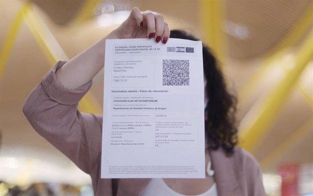 Archivo - Una mujer muestra el certificado COVID Digital de la Unión Europea