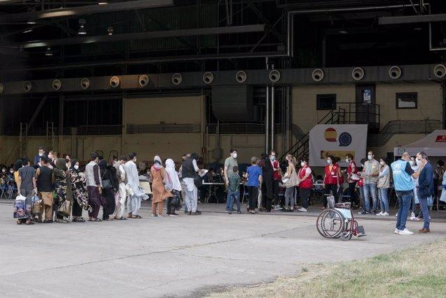Varios refugiados tras la llegada de un nuevo avión con 260 personas procedentes de Afganistán, en la base aérea de Torrejón de Ardoz, a 23 de agosto de 2021, en Madrid (España). Un total de siete aviones han salido desde el aeropuerto de Kabul hacia la b