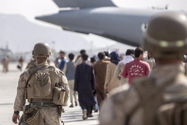 HANDOUT - 21 August 2021, Afghanistan, Kabul: US marine soldiers escort Afghan families at the Hamid Karzai International Airport during the evacuation of civilians following the Taliban takeover. Photo: Sgt. Samuel Ruiz/U.S. Marine/Planet Pix via ZUMA Pr
