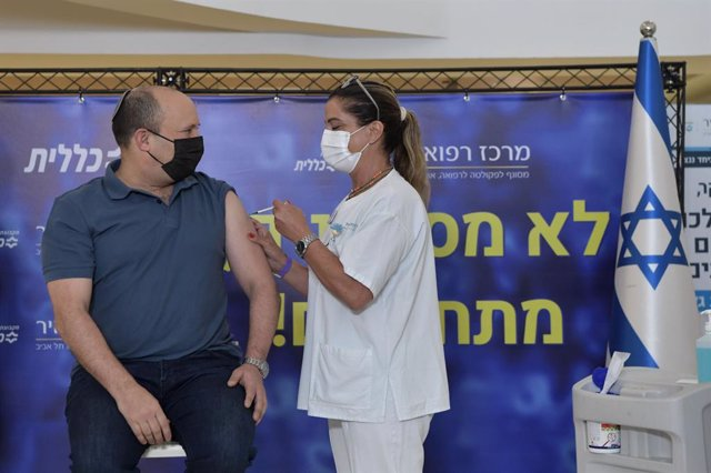 HANDOUT - 20 August 2021, Israel, Kfar Saba: Israeli Prime Minister Naftali Bennett (L)receives the third dose of the coronavirus vaccine at Meir Medical Center. Israel will give booster shots of the Covid-19 vaccine to people over the age of 40 from Fri