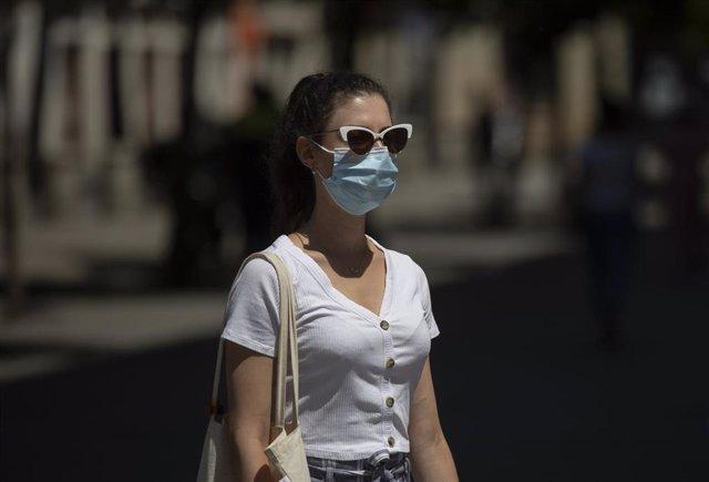 Archivo - Una mujer con mascarilla y gafas de sol en imagen de archivo