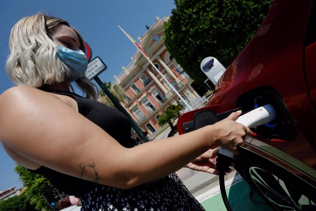 Una persona recarrega un cotxe elèctric en un punt de recarrega