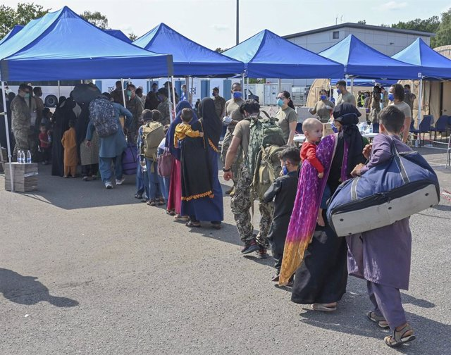 21 August 2021, Rhineland-Palatinate, Ramstein-Miesenbach: Afghan refugees evacuated from Kabul line up for processing after arrival from Kabul at Ramstein Air Base. Ramstein Air Base provides temporary housing for evacuees from Afghanistan as part of Ope