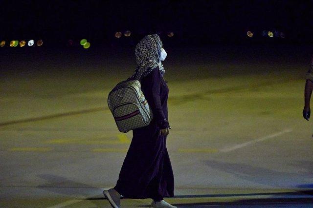 Una mujer repatriada camina a su llegada a la Base Aérea de Torrejón