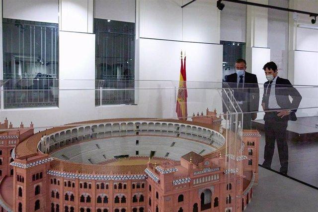 El consejero de Presidencia, Justicia e Interior de la Comunidad de Madrid, Enrique López (i), y el torero y director gerente del Centro Asuntos Taurinos de la Comunidad de Madrid, Miguel Abellán, observan una maqueta de la Plaza de Toros de las Ventas.