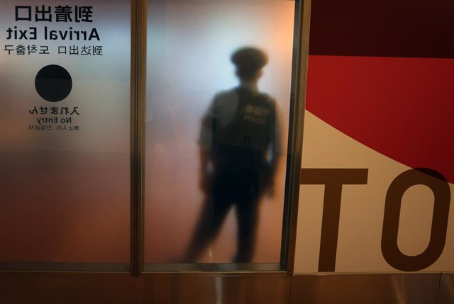 22 August 2021, Japan, Tokyo: A police officer stands in front of a frosted glass window at an exit for air travelers at Haneda Airport. Photo: Karl-Josef Hildenbrand/dpa