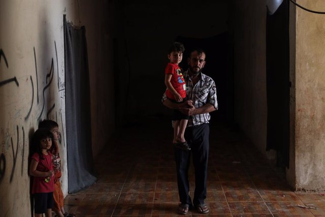 18 September 2021, Syria, Afrin: Apicture made available on 20 August 2021, shows 36-year-old Issam Al-Laham, who was displaced from Zamalka town in Eastern Ghouta, carrying his child in his makeshift house in Afrin. Al-Laham had survived the chemical at