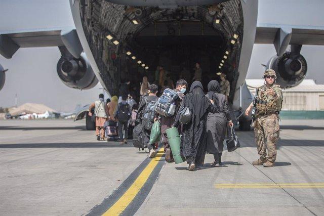 Pasajeros afganos suben al C-17 Globemaster III de la Fuerza Aérea estadounidense durante la evacuación de Afganistán en el aeropuerto internacional Hamid Karzai