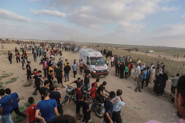 21 August 2021, Palestinian Territories, Gaza: Palestinian protesters evacuate injured youths amid clashes with Israeli security forces following a demonstration at the border fence with Israel, denouncing the Israeli siege of the Palestinian strip. Photo