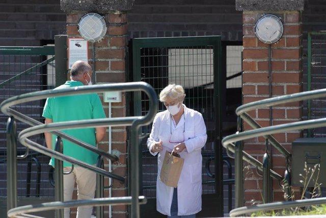 Una trabajadora atiende a un familiar en la puerta de la residencia de Las Gándaras, la mayor de Lugo.
