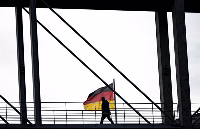 Archivo - 02 November 2020, Berlin: A man crosses the Marie-Elisabeth-Luders-House jetty in front of a German flag. The federal and state governments have decided on a partial lockdown. Photo: Fabian Sommer/dpa