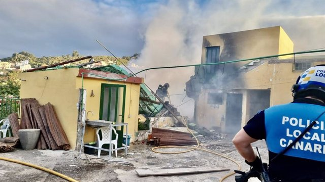 Un agente de la Policía Local de La Laguna observa el derrumbe de una vivienda tras un incendio
