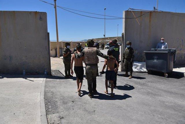 Archivo - Un militar del ejército español y un agente de la Guardia Civil ayudan a dos menores migrantes procedentes de Marruecos