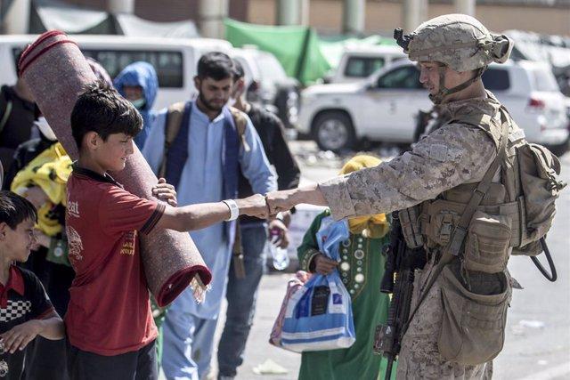 HANDOUT - 24 August 2021, Afghanistan, Kabul: A US marine fist bumps an Afghan boy during evacuation at Hamid Karzai International Airport following the Taliban takeover. Photo: Sgt. Samuel Ruiz/U.S. Marine/Planet Pix via ZUMA Press Wire/dpa - ATTENTION: