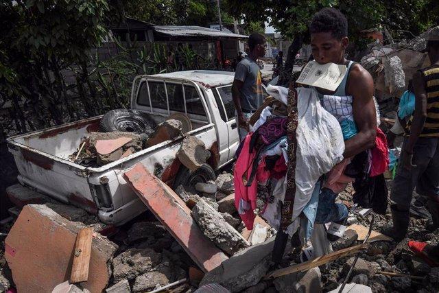 La gente rebusca entre los escombros tras el devastador terremoto de Haití