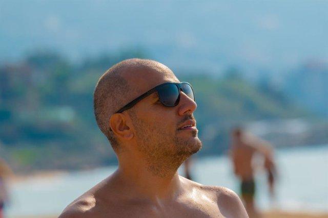 Archivo - Hombre con calva y gafas toma el sol en la playa.