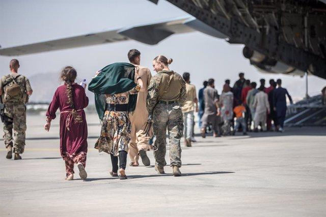 24 August 2021, Afghanistan, Kabul: A US marine escorts Afghan children during an evacuation at Hamid Karzai International Airport following the Taliban takeover. Photo: -/Planet Pix via ZUMA Press Wire/dpa