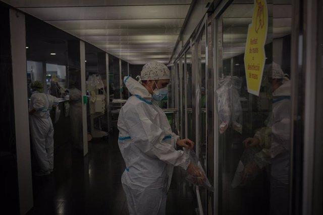 Archivo - Arxivo - Un treballador sanitari protegit en l'Unitat de Vigilància intensiva en una imatge d'arxiu.